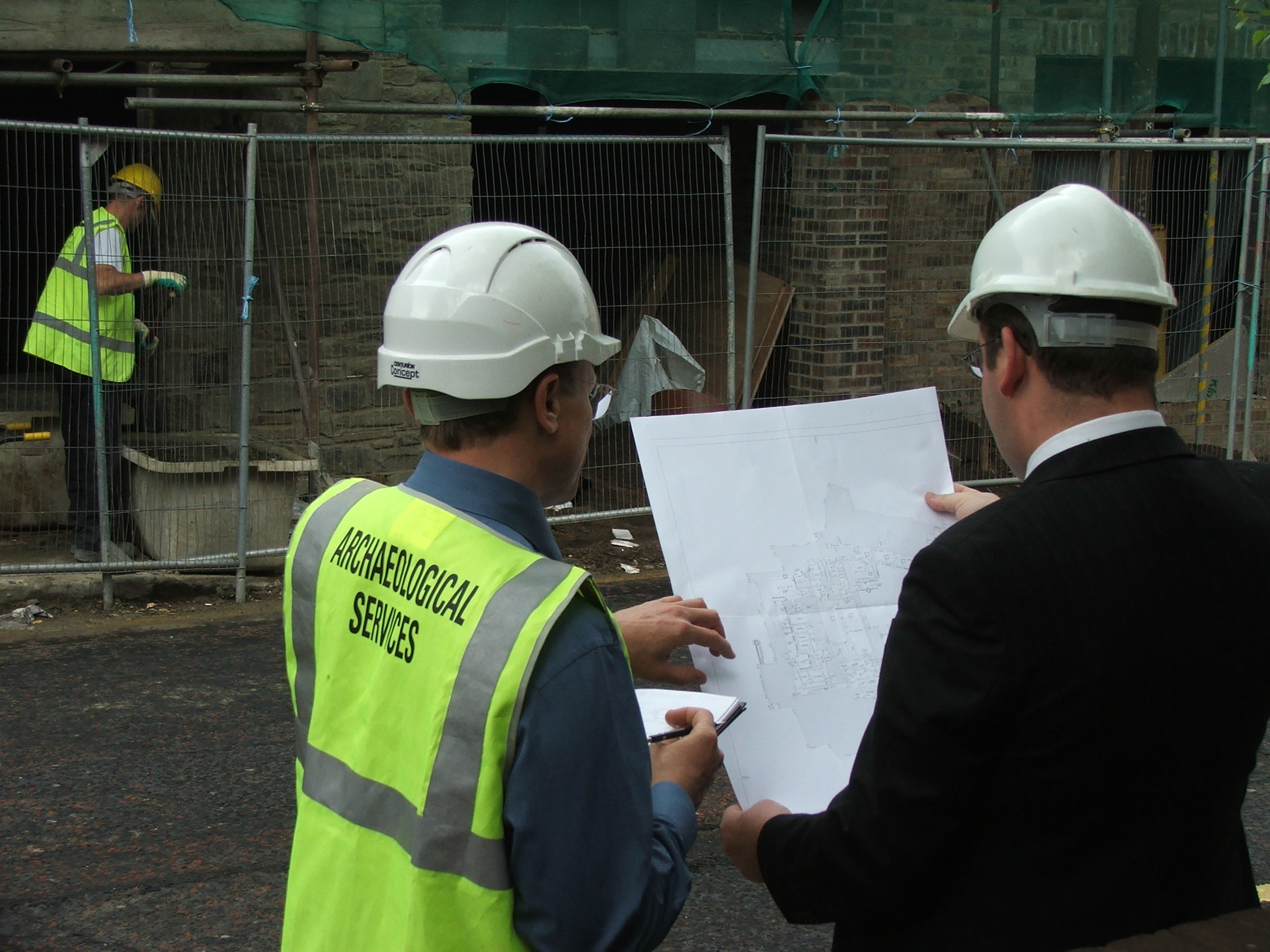 an archaeologist and a man in a suit looking at plans in front of building work on a historic building