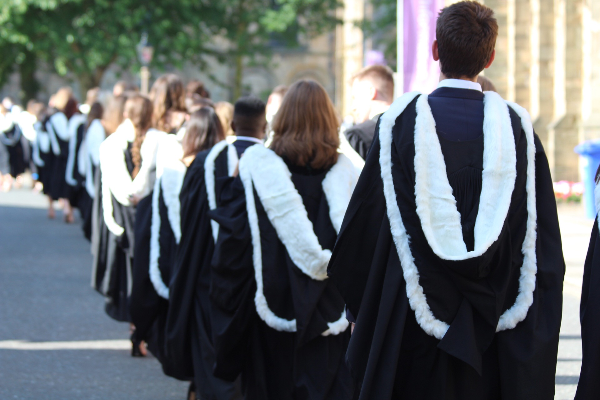 Students walking out of Durham cathedral wearing graduation robes