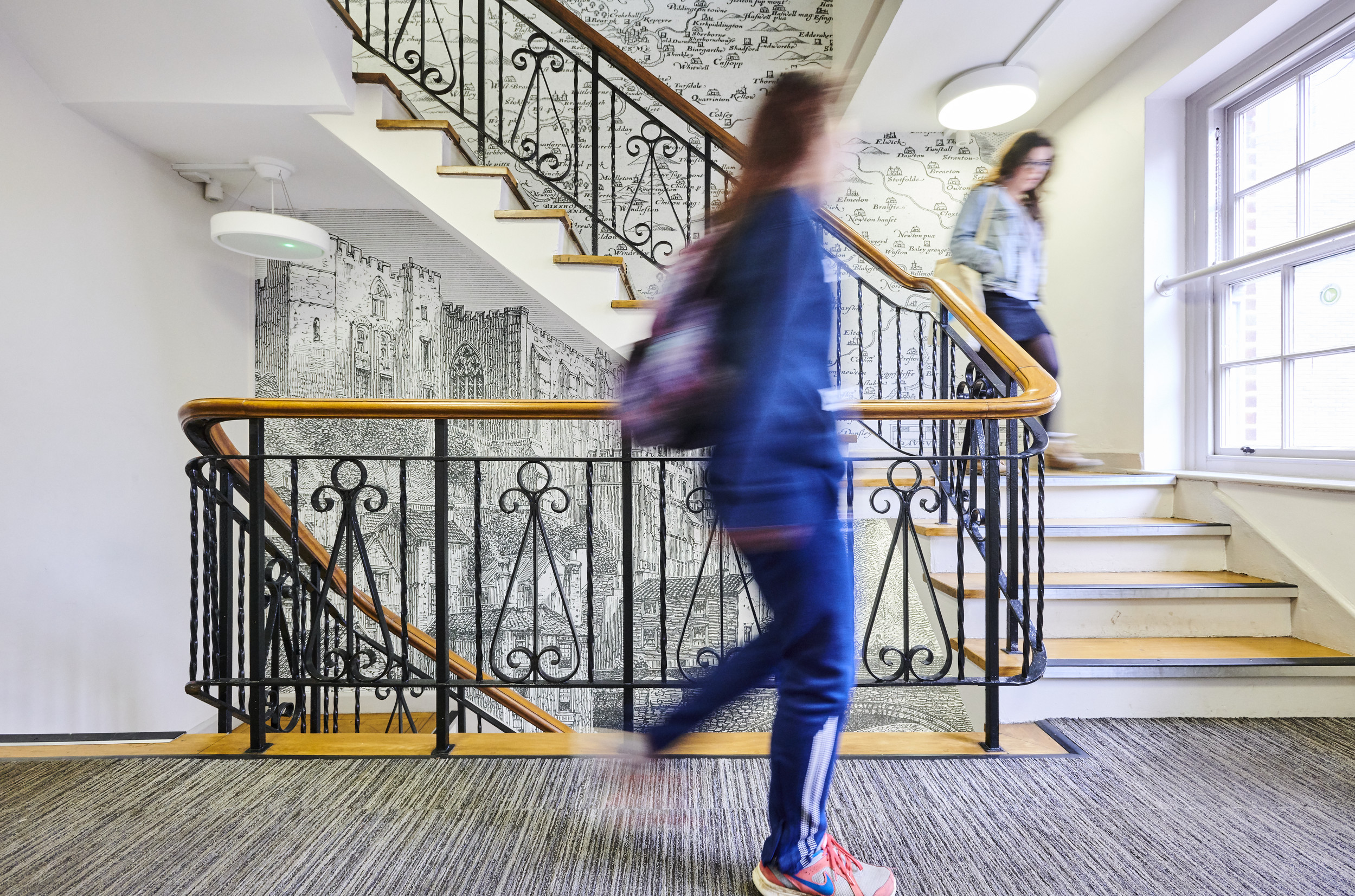 Students walking up a staircase inside the Department of History