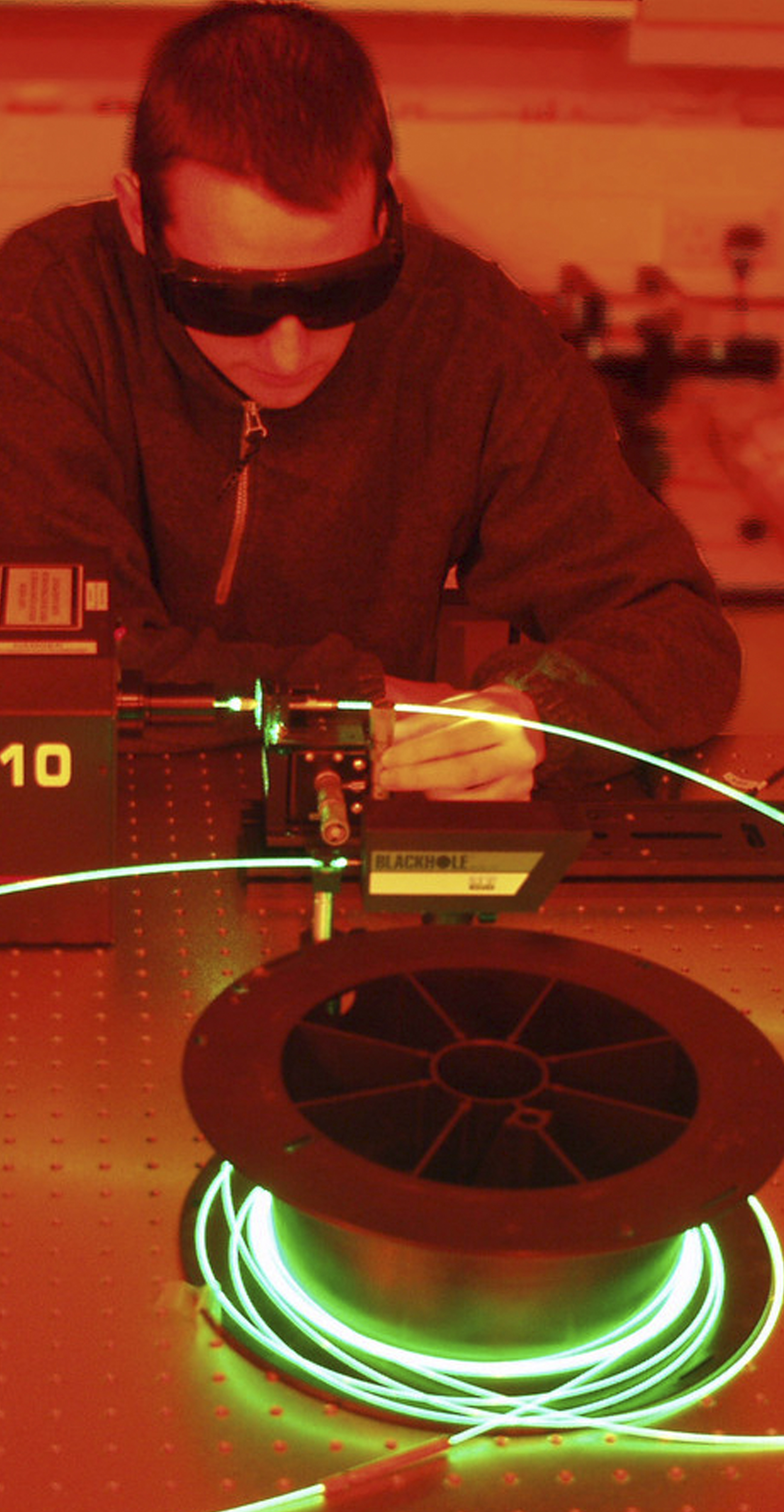 Student conducting a laser experiment in a darkened lab