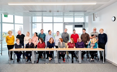 TDepartment staff sitting and standing around a table for a group photo